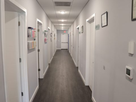 hallway with white painted walls and dark grey colored floor with multiple open doors and sleep medicine doctors office