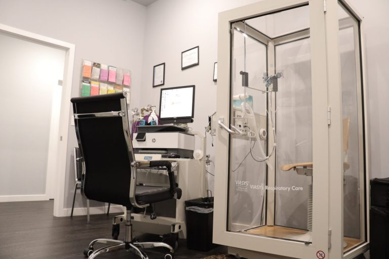 clear glass medical testing equipment and black office chair sitting next to computer and printer