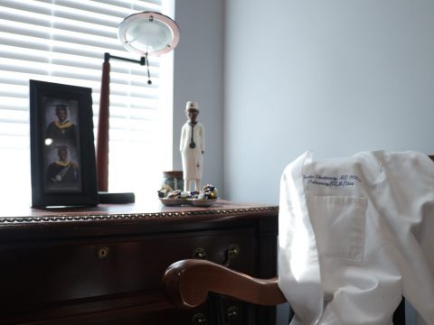 physician attire and personal belongings on desk